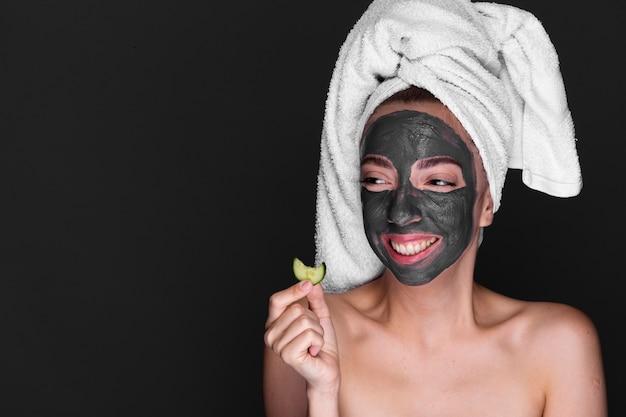 Volwassen vrouw met moddermasker op haar gezicht