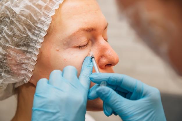 Volwassen vrouw met rimpels rond de ogen in procesverjongingsinjecties van hyaluronzuurvuller
