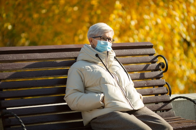 Volwassen vrouw ouder zittend op een bankje in de herfst het dragen van een medisch gezichtsmasker
