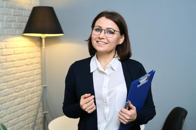 Volwassen vrouw psycholoog, psychiater, maatschappelijk werker met klembord kijken camera, achtergrond kantoor interieur