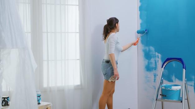 Volwassen vrouw schilderij muur met behulp van rolborstel gedoopt in blauwe verf. huisontwerper renoveren, renoveren. appartement herinrichting en woningbouw tijdens renovatie en verbetering. repareren en decoreren