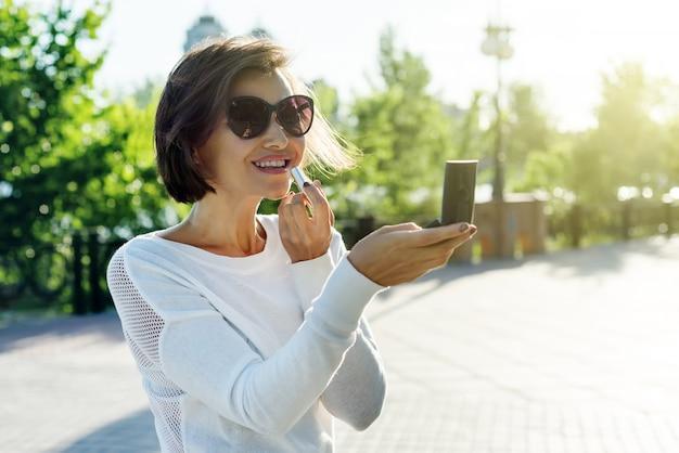 Volwassen vrouw schildert lippen met lippenstift