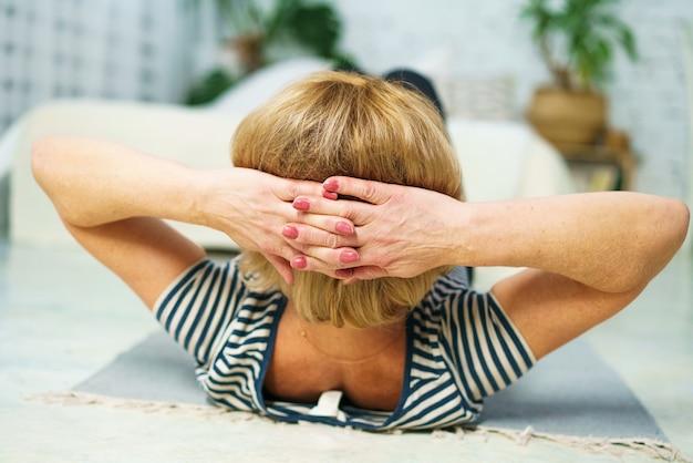 Volwassen vrouw van kaukasische verschijning in sportkleding thuis in de kamer houdt zich bezig met fitness tijdens het gezonde levensstijlconcept van volwassen mensen overdag