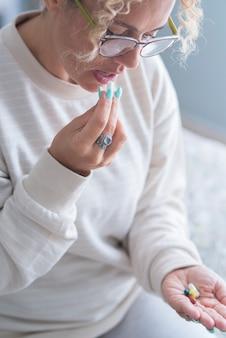 Volwassen vrouw van middelbare leeftijd die thuis pillen slikt en alleen op bed zit