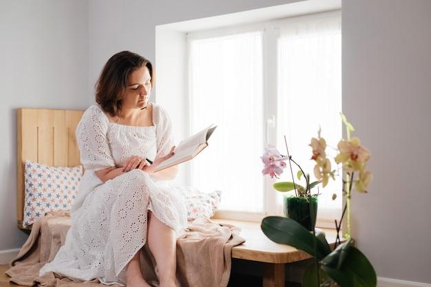 Volwassen vrouw van middelbare leeftijd plus maat die een boek leest bij het raam