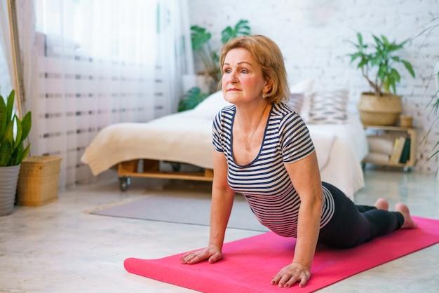 Volwassen vrouw van uiterlijk in sportkleding thuis in de kamer houdt zich overdag bezig met fitness