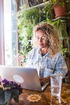Volwassen vrouw werkt op computerlaptop thuis in digitale slimme werkactiviteit glimlachen en schrijven