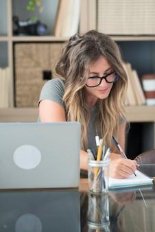 Volwassen vrouw werkt thuis aantekeningen maken en laptopcomputer gebruikt