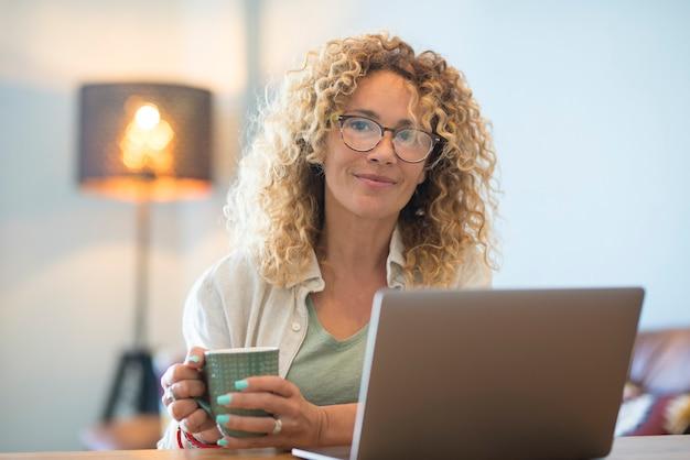 Volwassen vrouw werkt thuis, drinkt ontspannen en gebruikt een laptopcomputer - slim werken alternatief vrijheid kantoorleven - moderne mensen genieten van online werk - zakenvrouw beheert haar bedrijfsactiviteit alleen