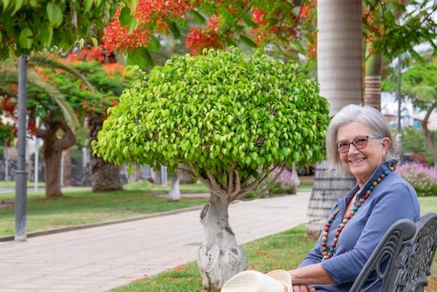 Volwassen vrouw witharige glimlachend zittend in het park op een bankje omringd door bloeiende planten
