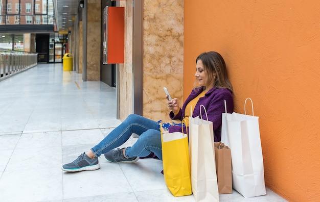 Volwassen vrouw zittend op de vloer kijken naar de mobiele telefoon met boodschappentassen naast haar