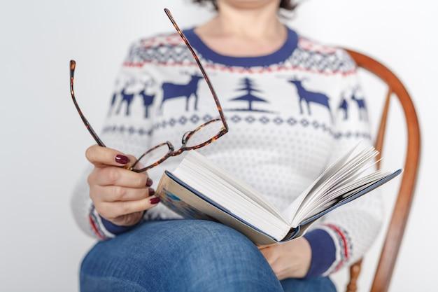 Volwassen vrouwelijk lezingsboek met in hand glazen