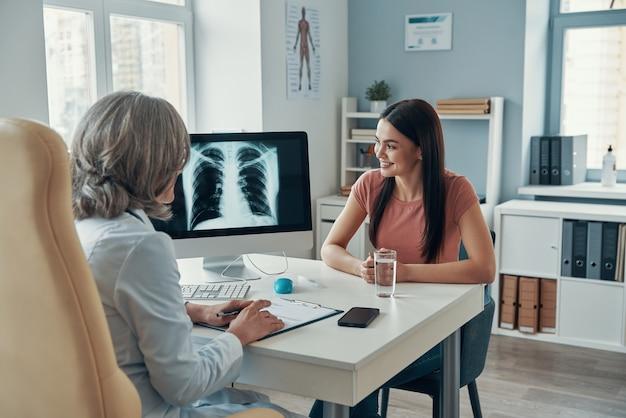 Volwassen vrouwelijke arts in witte laboratoriumjas die met jonge vrouw praat terwijl ze in haar kantoor zit