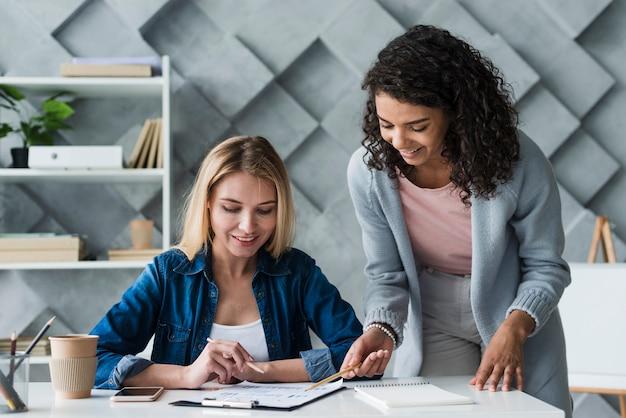 Volwassen vrouwelijke collega's die werkproject bespreken