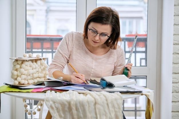Volwassen vrouwelijke ontwerper die met stofstalen werkt. vrouw zit aan bureau in de buurt van venster met tabletpallets van stoffen, materialen kiezen en maakt berekening