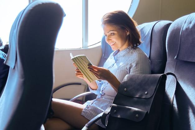 Volwassen vrouwelijke passagier zittend op een stoel in de buurt van raam in de veerbootcabine