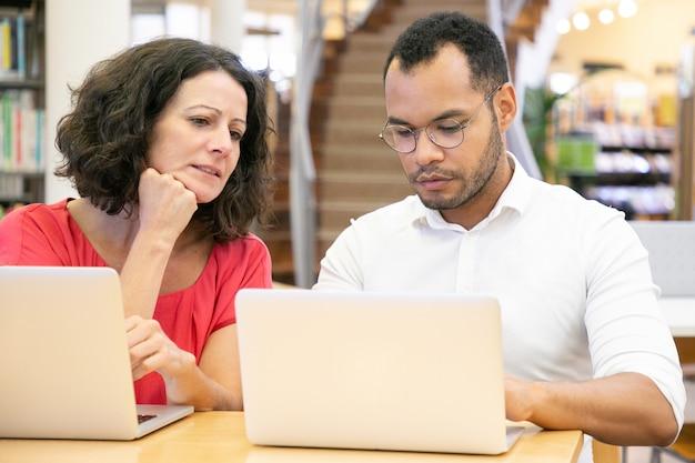 Volwassen vrouwelijke student die monitor van universiteitspartner bekijkt