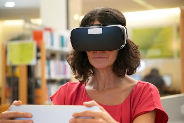 Volwassen vrouwelijke student die vr-hoofdtelefoon met behulp van terwijl het doen van onderzoek