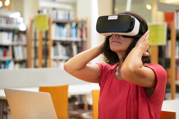 Volwassen vrouwelijke student opgewonden met virtuele presentatie