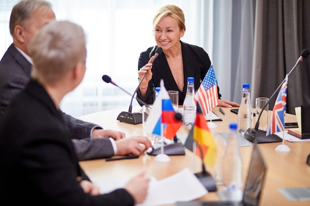 Volwassen vrouwelijke uitvoerende macht in formeel pak die toespraak houdt met politieke leiders van andere landen, diverse mensen verzamelden zich op persconferentie en ontmoetten elkaar zonder banden