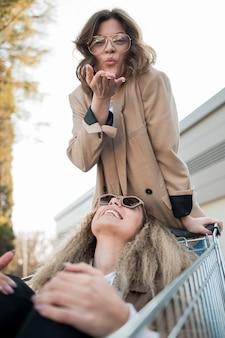 Volwassen vrouwen die met boodschappenwagentje spelen