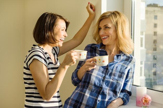 Volwassen vrouwen drinken koffie, praten, lachen