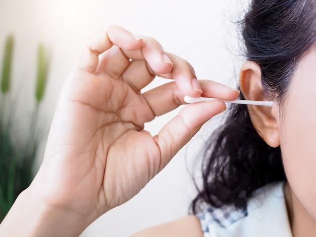 Volwassen vrouwen gebruiken wattenstaafjes die oorsmeer spinnen. close-up handreinigingsoor met wattenstaafje.