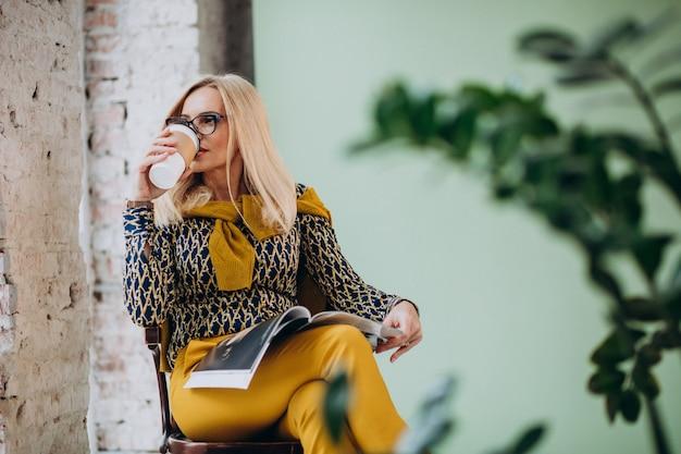 Volwassen vrouwenzitting als voorzitter het drinken koffie en het lezen van tijdschrift