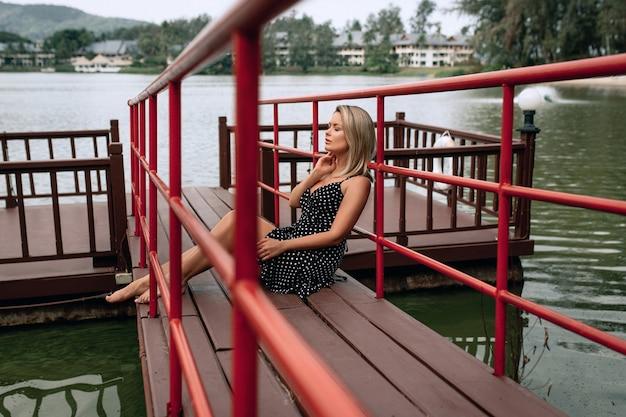 Volwassen vrouwtje in een zwarte jurk zittend op de pier en geniet van ontspannen
