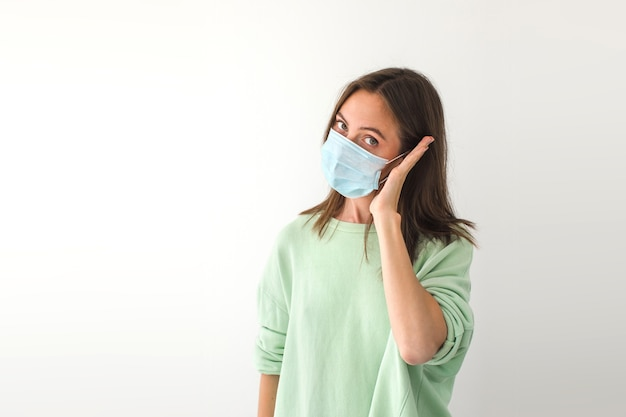 Volwassen vrouwtje in medisch masker die de handpalm dichtbij het oor houdt en naar de camera kijkt terwijl ze doet alsof ze belt tijdens een pandemie