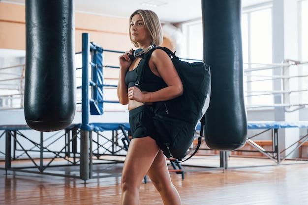Volwassen vrouwtje met zwarte tas en koptelefoon in de sportschool.
