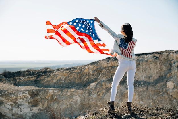 Volwassen wijfje die handen met de vlag van de vs opheffen