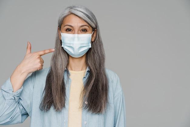 Volwassen witharige vrouw wijzende vinger naar haar gezichtsmasker geïsoleerd over grijze muur