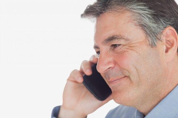 Volwassen zaken man glimlacht terwijl op oproep