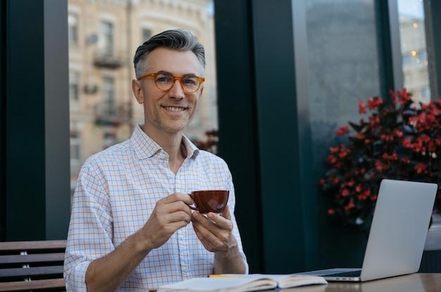 Volwassen zaken man koffie drinken in cafe, kijken naar camera, glimlachend