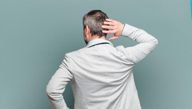Volwassen zakenman denken of twijfelen, hoofd krabben, zich verward en verward voelen, achter- of achteraanzicht