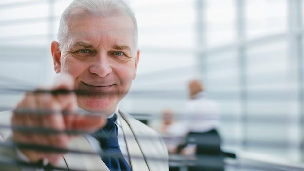 Volwassen zakenman die door de jaloezieën van het kantoor kijkt