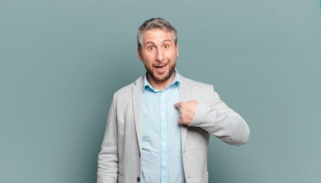Volwassen zakenman die er gelukkig, trots en verrast uitziet, vrolijk naar zichzelf wijst, zelfverzekerd en verheven is