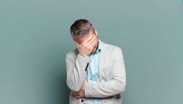 Volwassen zakenman die er gestrest, beschaamd of overstuur uitziet, met hoofdpijn, gezicht bedekt met hand
