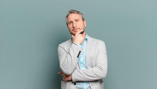 Volwassen zakenman die ernstig, bedachtzaam en wantrouwend kijkt, met één gekruiste arm en hand op kin, wegingsopties