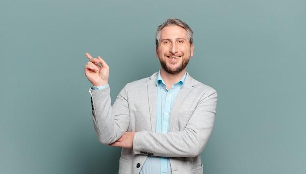Volwassen zakenman die gelukkig glimlacht en opzij kijkt, zich afvraagt, denkt of een idee heeft