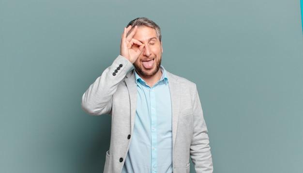 Volwassen zakenman die gelukkig met grappig gezicht glimlacht, een grapje maakt en door kijkgaatje kijkt, geheimen bespioneert