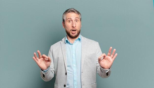 Volwassen zakenman die geschokt, verbaasd en verrast voelt, goedkeuring toont en goed teken met beide handen maakt