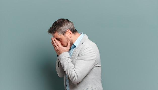 Volwassen zakenman die ogen behandelt met handen met een droevige, gefrustreerde blik van wanhoop, huilend, zijaanzicht