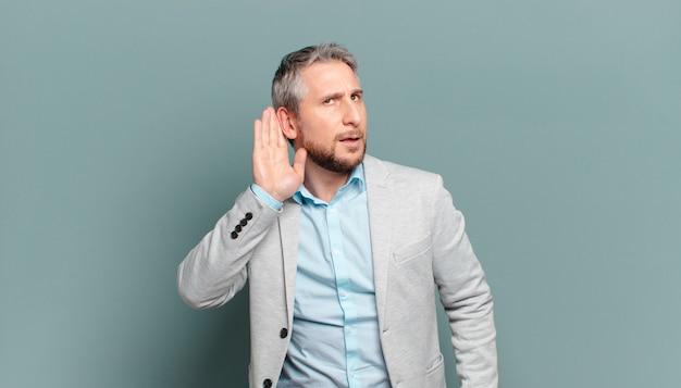 Volwassen zakenman die serieus en nieuwsgierig kijkt, luistert, een geheim gesprek of roddel probeert te horen, afluistert