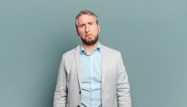 Volwassen zakenman die verdrietig en zeurderig is met een ongelukkige blik, huilt met een negatieve en gefrustreerde houding