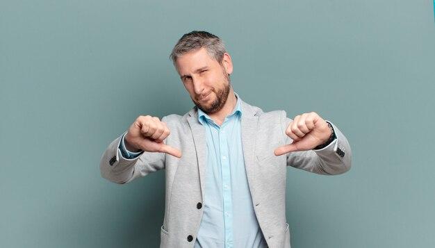 Volwassen zakenman die verdrietig, teleurgesteld of boos kijkt, duimen toont in onenigheid