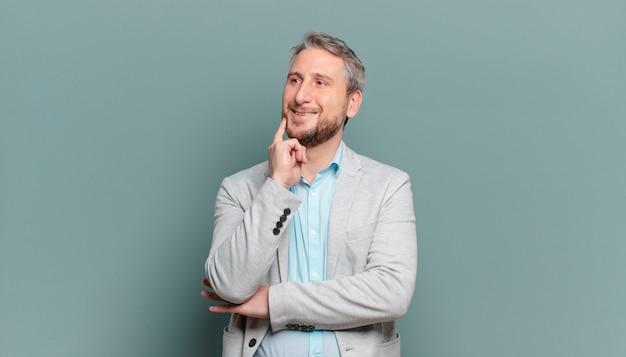 Volwassen zakenman die vrolijk lacht en dagdroomt of twijfelt, opzij kijkend