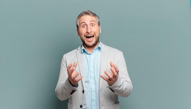 Volwassen zakenman die wanhopig en gefrustreerd, gestrest, ongelukkig en geïrriteerd kijkt, schreeuwt en schreeuwt