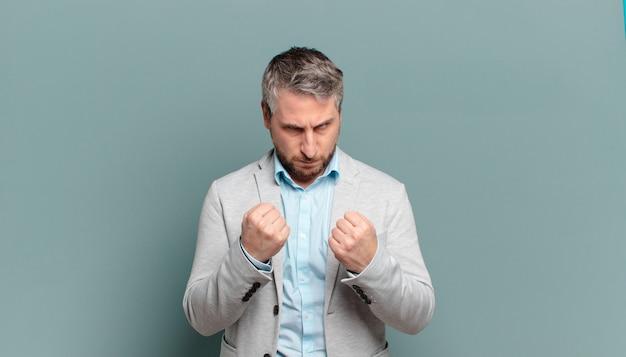 Volwassen zakenman die zelfverzekerd, boos, sterk en agressief kijkt, met vuisten klaar om te vechten in bokspositie